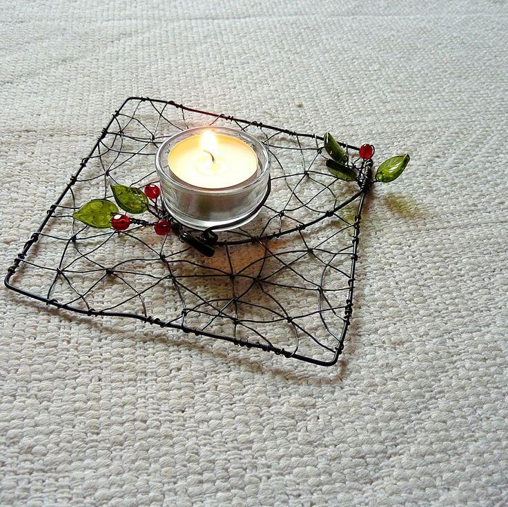 Hranatý svícen Drátovaný svícen, který je zajímavý svým tvarem. Díkyskleněnému kalíškuje bezpečný a vhodný na čajovou svíčku. Výborně vypadá i jako dekorace. Je vyroben z černého žíhaného drátu a dozdoben kvalitními korálky české výroby - kuličky, lístečky. Rozměry cca 13 x13 cm Na přání lze vyrobit i v jiném barevném provedení.  Návrh i ...