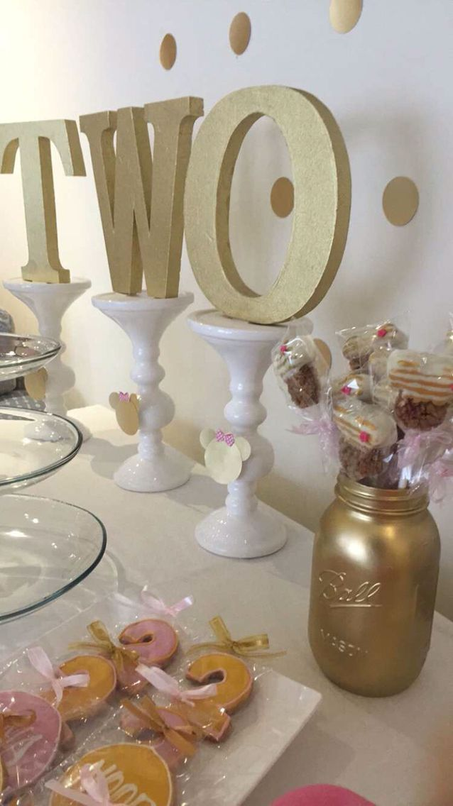 """Spray painted word """"two"""" on candle holders with minnie cutouts. Spray painted mason jars gold for flowers. Pink and white Minnie mouse Rice Krispies treats. Pink & Gold minnie mouse Birthday party"""