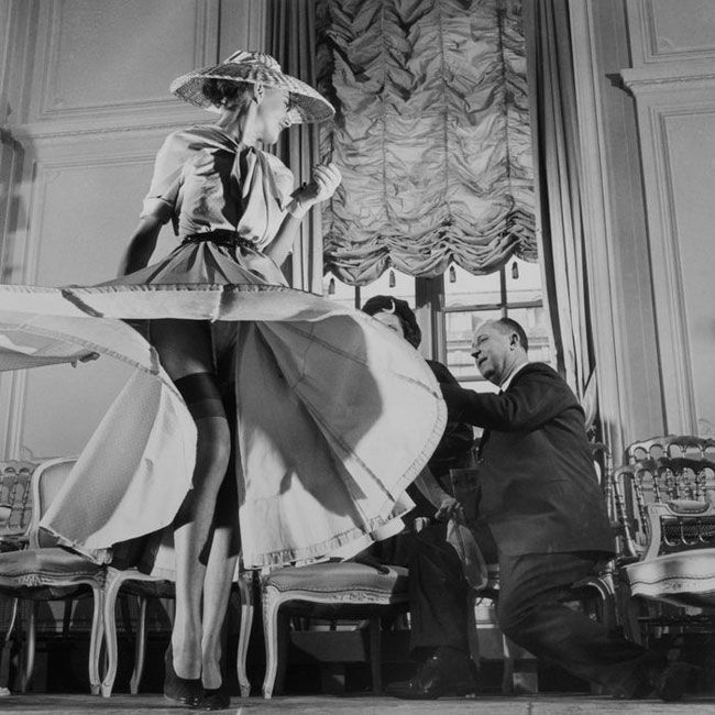 "Christian Dior himself, inspecting a ""New Look"" dress on a model.  Note that the skirt is made of many gores (pieces) to eliminate what is commonly called ""bias sag"" and to regularize the orientation of any nap or grain on the fabric throughout the piece."