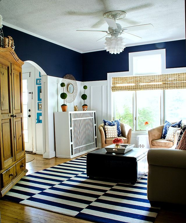 Navy and white living room. Coastal decor ideas in living room. Navy walls. Board and batten walls in living room. Navy and white striped rug. Coral accents
