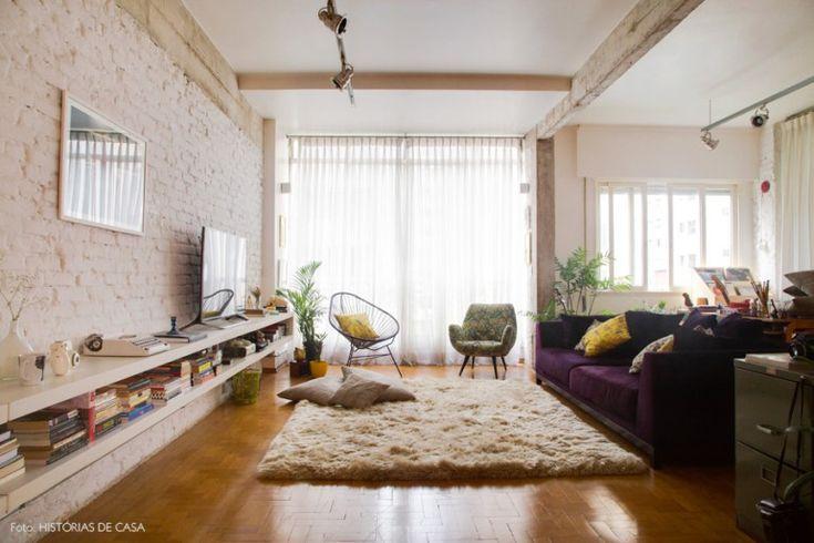 Sala de estar com sofá roxo, tapete neutro e parede de tijolinho branco.