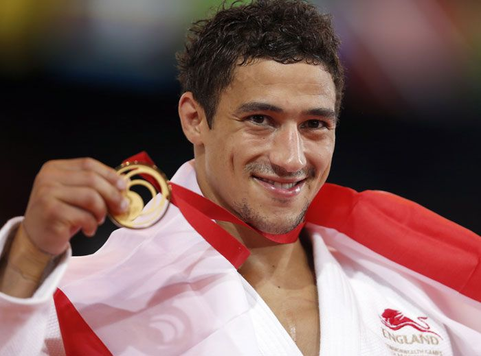 England's Ashley McKenzie shows off his gold medal after winning his Judo final bout.