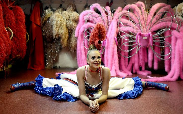 A dancer of the Moulin Rouge cabaret stretches prior to a show in Paris, France