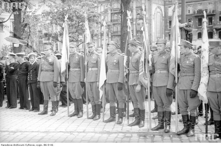 Poczet sztandarowy - żołnierze z odznaczeniami. Z lewej marynarze Marynarki Wojennej i drogowskaz w języku rosyjskim.