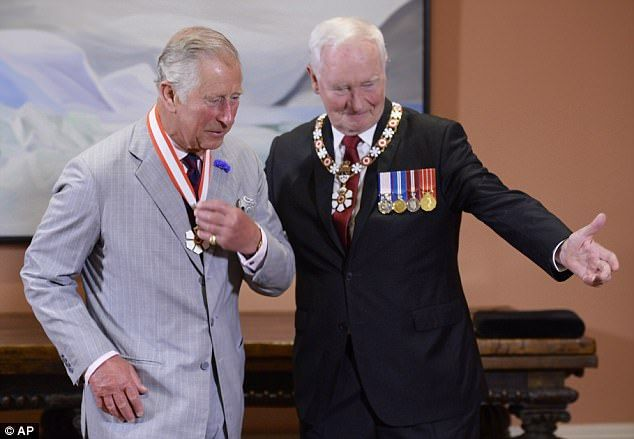 Prince Charles, left, receives the Extraordinary Companion to the Order of Canada medal fr...