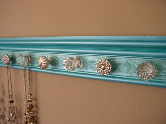 jewelry/necklace  organizer with 7 decorative cabinet knobs on metallic teal with embossed background 20  inches long