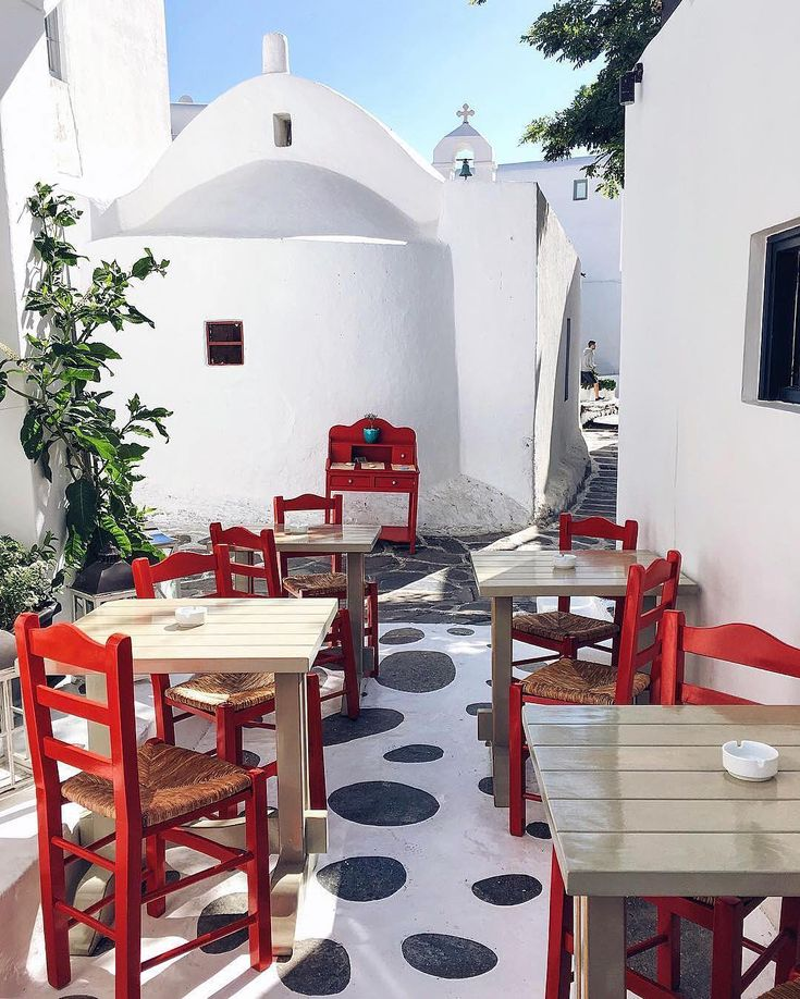 Mykonos island (Μύκονος)❤️. Colorful Cycladic style corner with the beautiful white church at the background !!