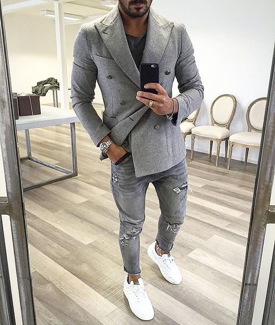 Perfect the smart casual look in a grey double breasted blazer and grey ripped jeans. Dress down this getup with white low top sneakers.   Shop this look on Lookastic: https://lookastic.com/men/looks/double-breasted-blazer-crew-neck-t-shirt-jeans/19290   — Black Crew-neck T-shirt  — Grey Double Breasted Blazer  — Silver Watch  — Grey Ripped Jeans  — White Low Top Sneakers