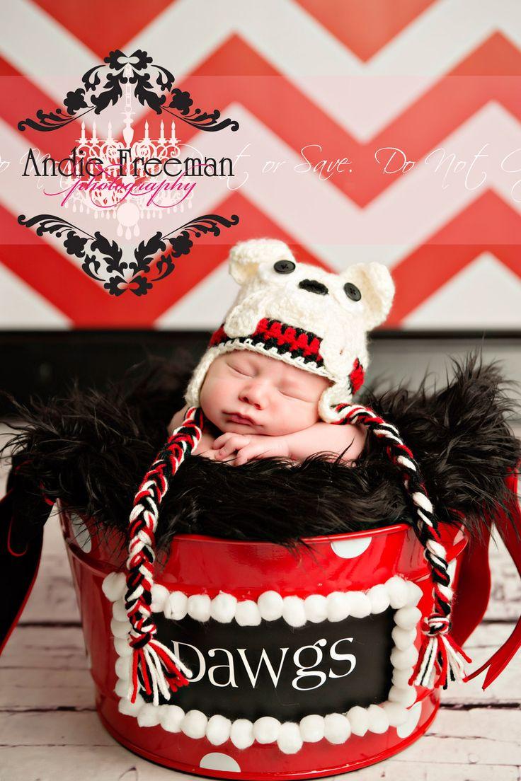 Newborn baby boy wearing Georgia Bulldogs hat in University of Georgia bucket in front of red and white chevron backdrop.   www.TheAthensNewbornPhotographer.com