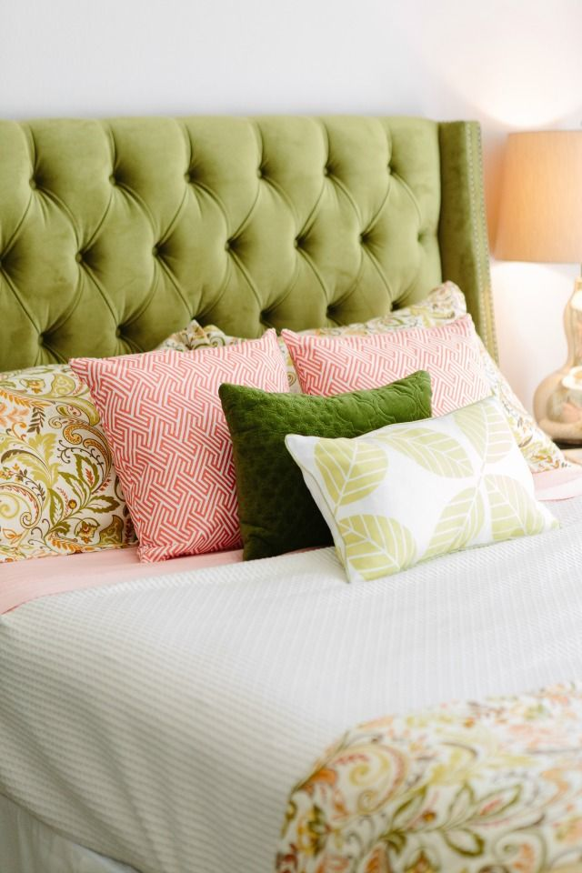 That headboard! Rich green paired with coral and blush accents