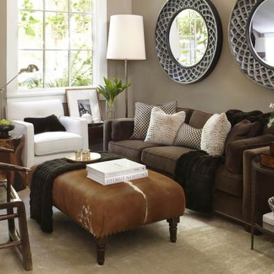 brown couch with grey and white cushions and cow puff
