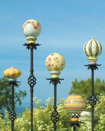 MacKenzie-Childs ceramic garden balls on sticks.  Oh, I do think I'll tweak this and do it myslef!  Garage sale curtain rods, a little mosaic or stacked glass....