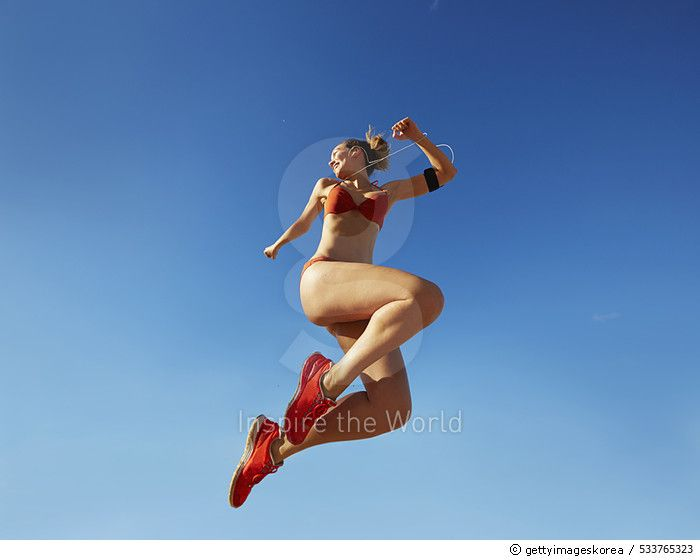 Pacific Islander woman jumping for joy under blue sky - gettyimageskorea