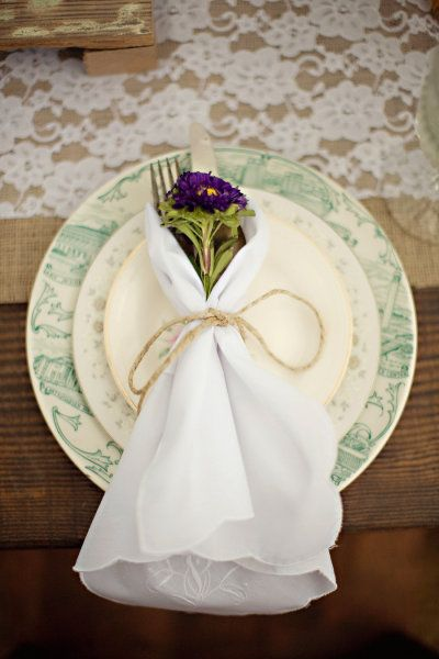 simple place setting with white napkin, purple flower and silverware ties with twine