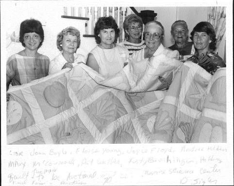 """L to R Joan Boyle, Eloise Young, Joyce Floyd, Andree Holden, Mary McCormack, Pat Walker, Rusty Berihinger, holding quilt they made to be auctioned off at Marine Science Center fund raising auction."" October 6th, 1985."