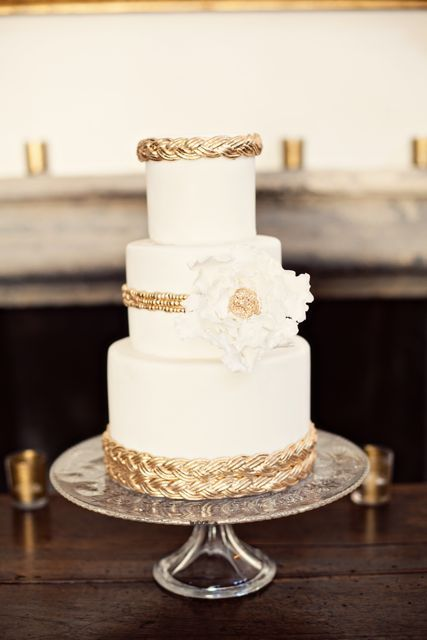 Clean and modern, rich and elegant wedding cake with white and gold color scheme. Gold braids fondant were used to wrap around the cake tiers. Decorated with white ruffle sugar flower with a large gold center.