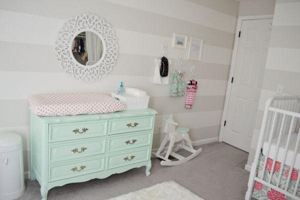 baby girl nursery: mint french provincial changing table/dresser, vintage white wall hooks, striped walls, jenny lind crib, mint and coral