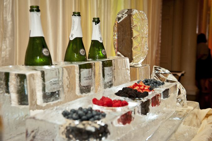 """If your venue includes a 'custom ice sculpture' in its catering package, don't be so quick to turn it down!  Ask if they can carve cylindrical holes into ice blocks to create your own champagne bar.  Champagne bottles and frozen fruit stay cold, and your guests are treated to a unique experience.""  