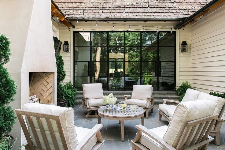 Chic courtyard is filled with gray wash teak accent chairs placed in a circular formation surrounding a round gray wash outdoor coffee table placed before a white stucco fireplace.