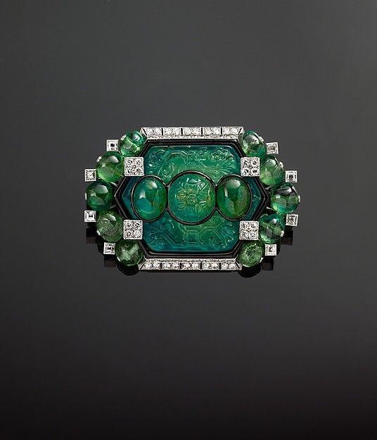 Brooch with Carved Emeralds and Diamonds by Cartier Cartier  (French, founded Paris, 1847) Object Name: Brooch Date: 1925, modified by Cartier in 1927 Geography: France, Paris Medium: Platinum, set with emeralds, diamonds, and enamel Dimensions: Height: 1 3/4 in. (4.4 cm) Width: 2 5/8 in. (6.7 cm) Hexagonal diamond: approx. 88.03 ct; Central curved cabochon emerald: approx. 15.65 ct Classification: Jewelry Credit Line: The Al-Thani Collection