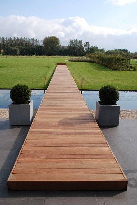 Houten tuinpad van terras over water naar gras in Afrikaans padoek© Belgian Woodforum