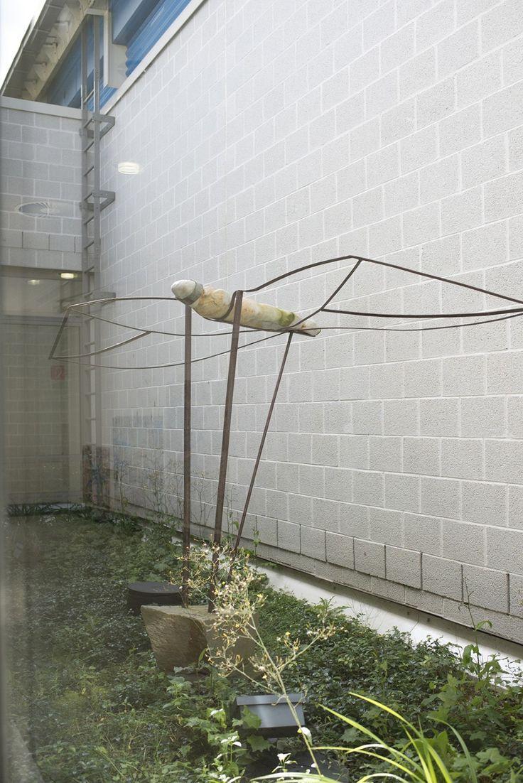 #Kiel Wie eine Libelle ist die Figur im verglasten Innenhof des Hörsaalgebäudes gefangen: ein stilisierter menschlicher Körper mit metallischen Flügeln, die von einem steinernen Fuß am Boden gehalten wir...
