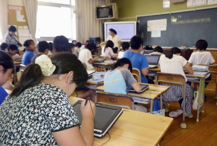 Students at Fujinoki Elementary School in Hiroshima use tablet computers in class last July. The government is considering introducing digital textbooks as more classrooms become digitized.