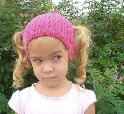 "This girl doesn't look too happy wearing a ""Piggle"" - but isn't it the cutest idea - a little girl's hat with two holes on the sides for pigtails! Free pattern! Light/DK yarn."