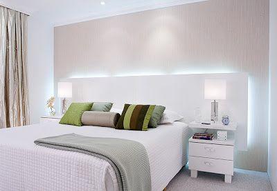 Quarto Branco com cabeceira lisa de mdf com iluminação embutida (fluorescente). Detalhes de cor apenas nas almofadas. A luz branca da uma idéia meio futurista, mas o quarto permanece aconchegante.