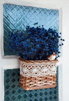 Bonitas e delicadas, as flores têm a vocação natural de tornar os cantinhos mais agradáveis. Então, aproveite essa característica logo na entrada. Aqui, um cesto de vime (Artesanato Barigui, R$ 6), decorado com uma renda de algodão, exibe ramos de flores secas azuis (Daiara Artes, R$ 2,90 cada ramo). Um pássaro de madeira dá o toque final ao conjunto rústico. Para fixar, martele um prego por dentro da cestinha.