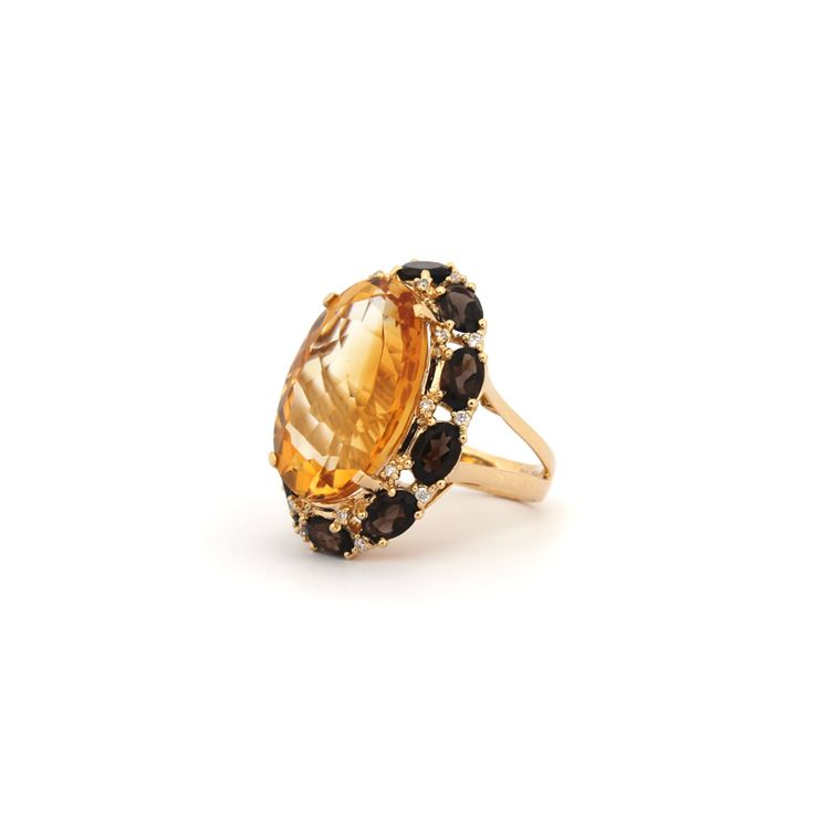 Eau de Vie Ring   This glamorous ring is made with a spectacular centre stone of Citrine, surrounded by a ring of smokey quartz and diamonds set in 18 karat yellow gold.
