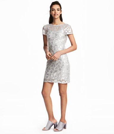 Silver. En kort, figurnära klänning i transparent, vävd kvalitet med paljetter. Klänningen har vid halsringning och kort holkärm. Innerklänning i trikå med