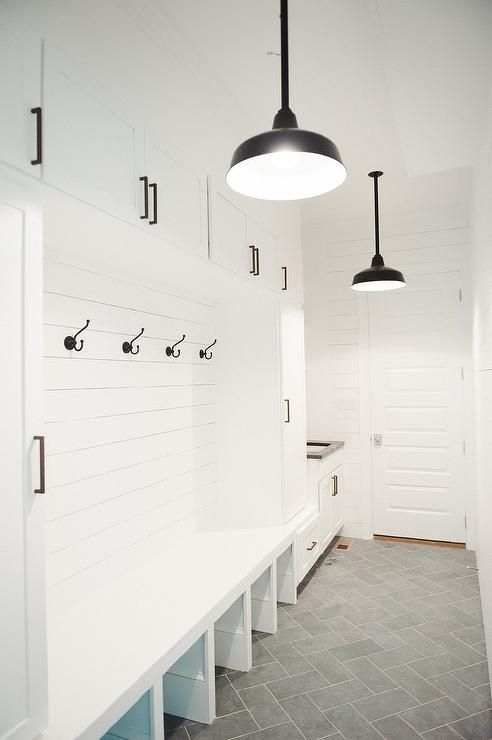 Fabulous cottage mudroom features white built-in cabinets adorned with oil rubbed bronze hardware ...