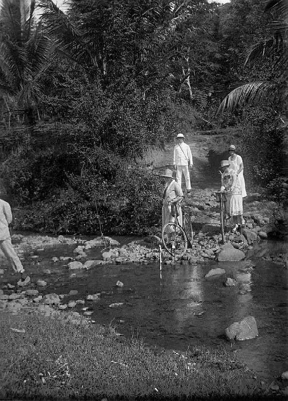 Europees gezelschap steekt met de fiets een rivier over bij Plipir nabij Poerworedjo. 1928