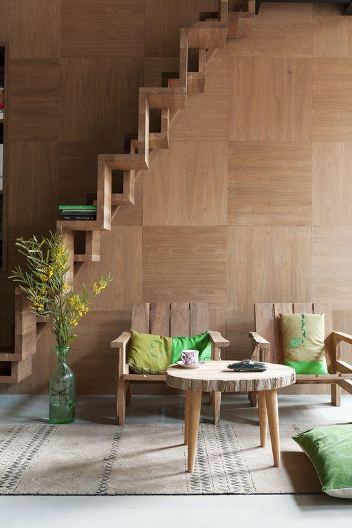 Bij een strakke gietvloer of robuuste vloer van betonwerkt een houten wandbekleding heel goed.