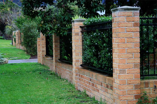 Brick fence by Robert Wojciechowski, via Flickr Hedges through fence to add privacy