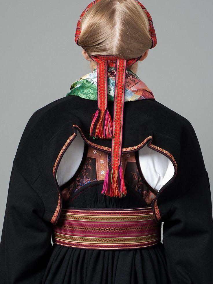 Fin beltestakk med en kort jakke som viser beltet fra baksiden. Foran er jakka lenger og skjuler det meste av fargene.