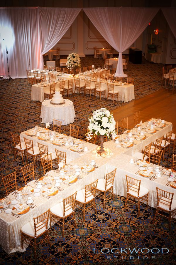 """Long, rectangular reception tables are a popular choice, but that often means you'll have to spend a fortune on centerpieces cascading down the middle of the table. That's why we love this """"X"""" setup instead — you can fit 30+ people at one table, with just one centerpiece in the middle!"""