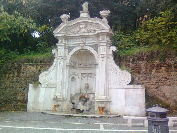 La Fontana del Prigione. In 1923 it was moved again to the intersection of Via G. Mameli & Via L. Manara in Trastevere. It consists of a central niche flanked by  two pilasters supporting a decorated pediment. The water flows into two small pools at the base of the pilasters, & a lion's head at the back of the niche spits water into a central pool at street level. On the top is a statue of Asclepius, the god of medicine, but he seems to have lost his head.