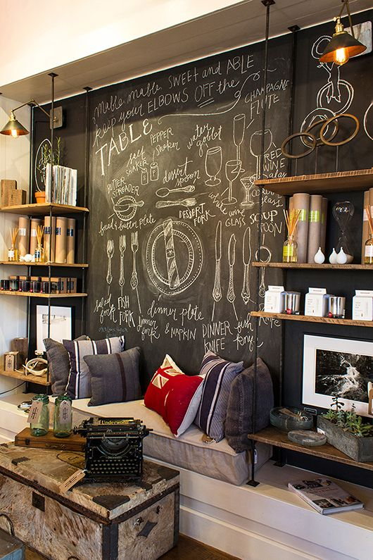 industry-home; chalkboard wall behind shop display. Such a cool industrial look behind shelving & would work at home as well!
