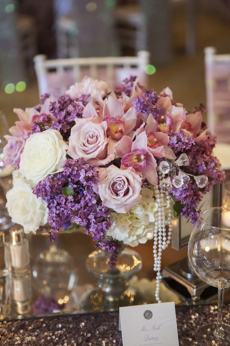 Long tables were swathed in lavender sequined linens and topped with arrangements of ivory hydrangeas, violet roses, and blush orchids accented with pearls and crystals. #floralarrangement Photography: Christine Bentley Photography. Read More: http://www.insideweddings.com/weddings/pastel-pink-purple-celebration-at-the-resort-at-pelican-hill/591/