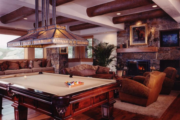 Here's another grand, rustic look family room, combining stone walls, large log-style exposed beams overhead, and a rich palette of earthy browns throughout. Ornate billiards table stands below a custom stained glass lighting solution, while fireplace at right holds a singular natural wood mantle.