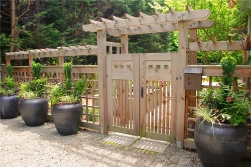 I love the clean simplicity of this wooden arbor and gate. The repetition of the modern-looking pots balances the unfinished wood perfectly. Design by Exteriorscapes in Seattle, WA. Get more ideas for garden gates here: http://www.landscapingnetwork.com/fencing/gates.html