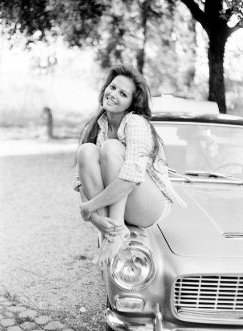 Claudia Cardinale posing atop a car
