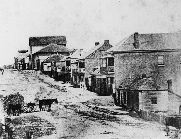 Photograph taken from the corner of Edward Street and Queen Street, looking south. The large building visible at the top of the rise on the right was originally the convict barracks, constructed in 1827 - 1828 and demolished in 1881. In the far distance, on the corner of George Street, is Dr Hugh Bell's residence, erected in 1857, and demolished in 1906. The two-storey buildings in the foreground were the North Brisbane Hotel on the left and R. A. Kingsford's store on the right. Most of the…