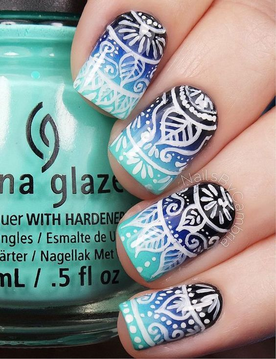 Tribal nail art design on top of a blue gradient theme. Dark and light blue are used for the gradient effect while white polish is used for the tribal designs on top.: