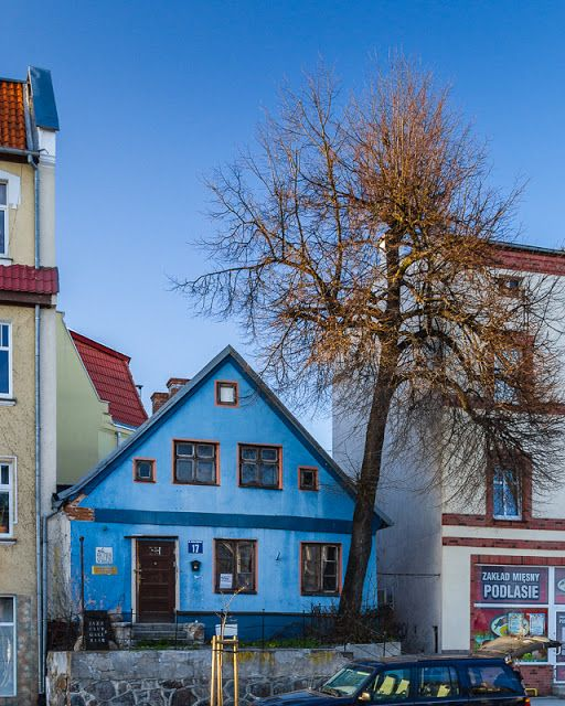 An old blue house with a tree in Gizycko, Masuria Lake District, Poland