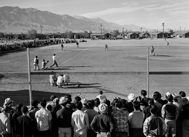 Baseball game at Manzanar War Relocation Center, Owens Valley, California, 1943, Ansel Adams, public domain via Wikimedia Commons.