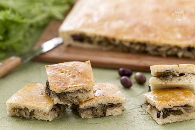 La pizza di scarola, di origine campana, è una fragrante focaccia farcita, realizzata con un ripieno a base di insalata scarola, capperi e olive.