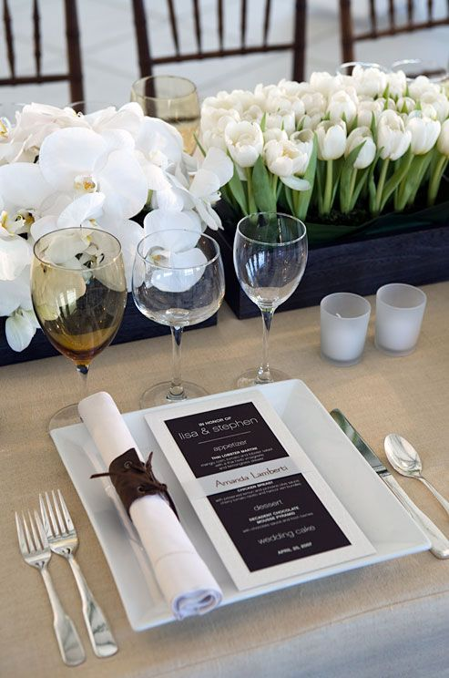 lovely table setting of white orchids and tulips in black boxes